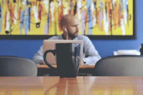 En fyr på en kaffebar som jobber på sin datamaskin
