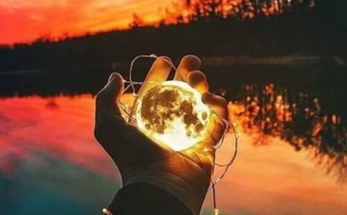 En person på en innsjø med månen i hånden