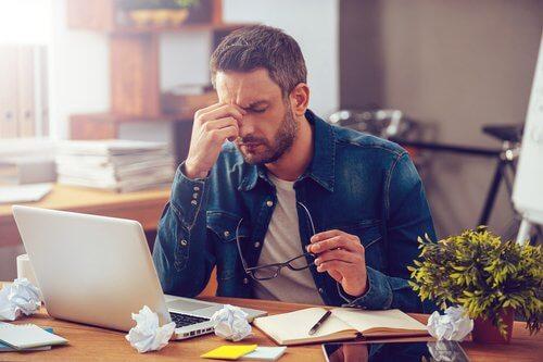 Typer prokrastinering: En mann som jobber hardt på sin datamaskin