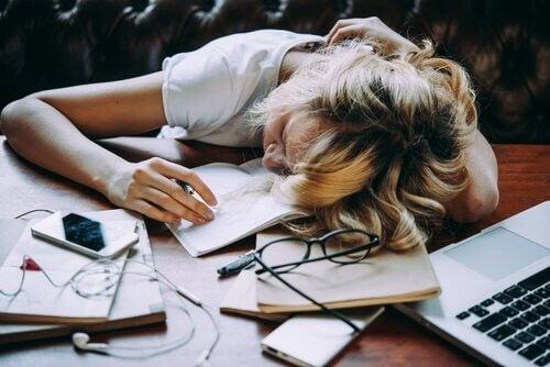 Trøtt kvinne med hodet på pulten.