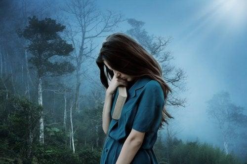 En kvinne med depresjon i skogen
