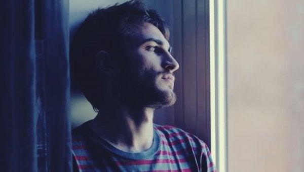 En trist 30 år gammel mann ser ut av vinduet