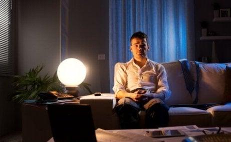 Mann med søvnløshet sitter i sofaen