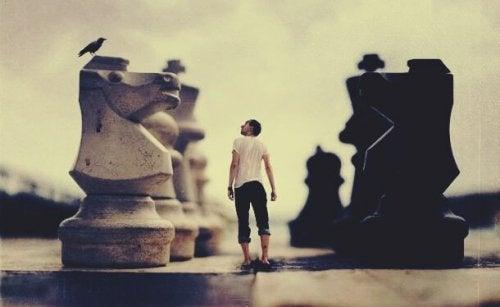 En mann omgitt av gigantiske sjakkbrikker