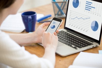 Kvinne sjekker statistikk på sin bærbare datamaskin