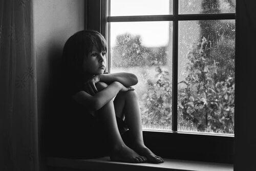Trist barn ser gjennom vinduet.