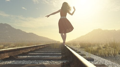 Jente går langs jernbanespor
