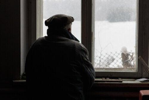 En gammel mann stirrer ut av vinduet
