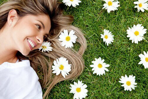 En kvinne som ligger ved siden av blomster og smiler