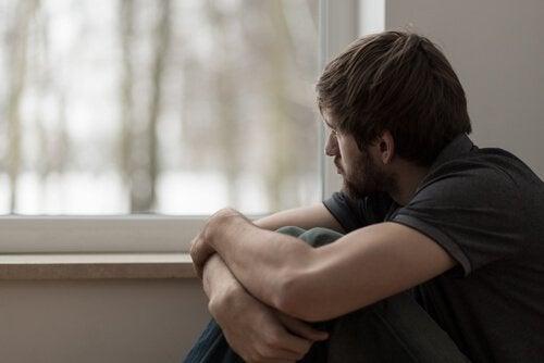 En bekymret mann ser gjennom vinduet.