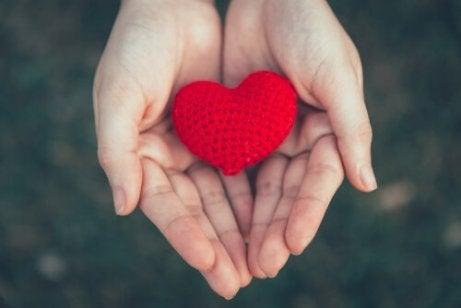 To hender som holder et heklet hjerte