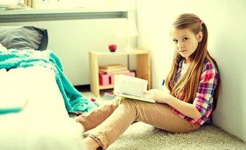 En jente leser i rommet hennes.