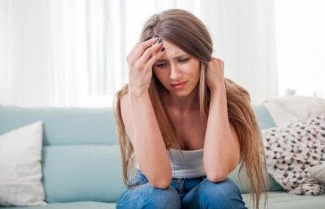 En kvinne sitter ned, sint på seg selv