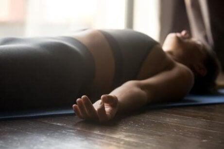 En kvinne som praktiserer mindfulness som ligger på gulvet i en tilstand av avslapning