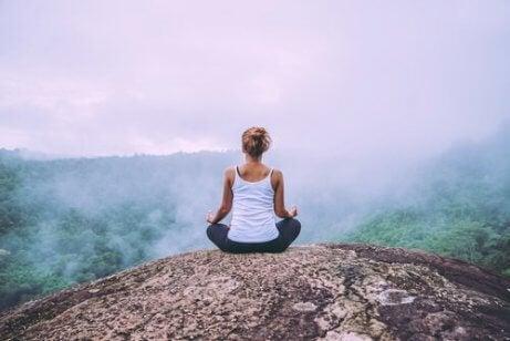 En kvinne som mediterer på et fjell