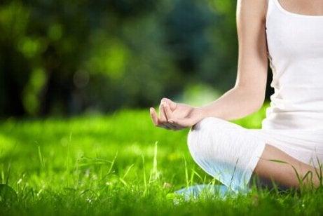 En kvinne mediterer i gresset