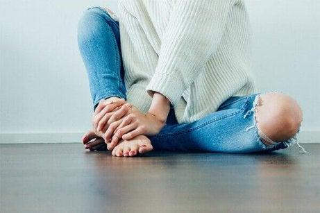 En kvinne som sitter på gulvet
