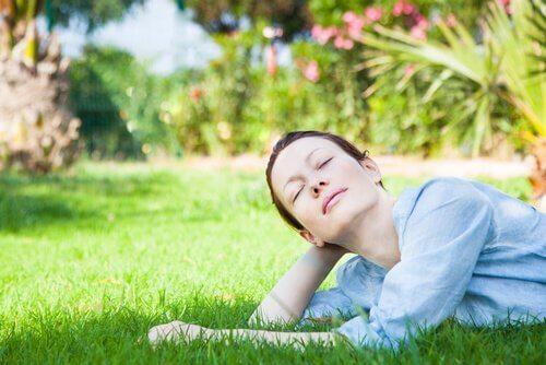 Kvinne ligger i gresset og tenker på hva hun elsker