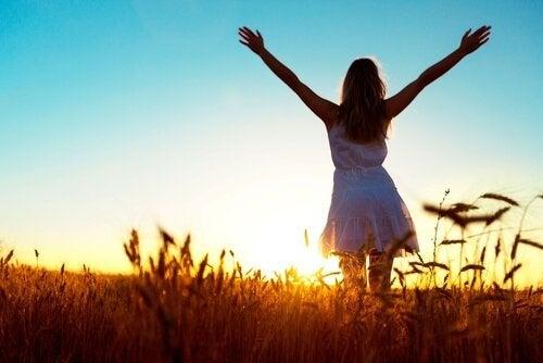 En glad kvinne med åpne armer ved solnedgang.