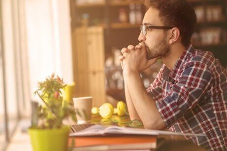 En mann sitter foran datamaskinen og tenker på hva det betyr å ha holdning