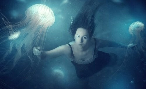 Kvinne under vann med maneter