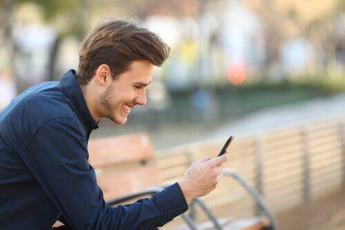 Mann driver med nettdating og smiler mot telefon