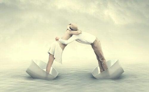Mennesker omfavner hverandre i hver sin båt