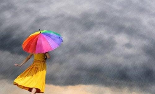 En kvinne med en fargerik paraply under en storm