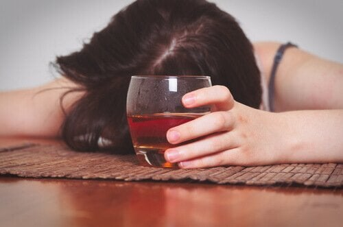 En kvinne med et glass full av alkohol