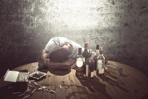 En mann med alkoholforstyrrelser omgitt av flasker av alkohol