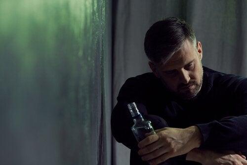 En trist mann som holder en flaske alkohol