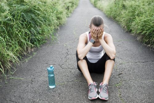 En utmattet løper med overtreningssyndrom sitter på bakken.