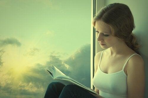 Jente leser bok ved vinduet.