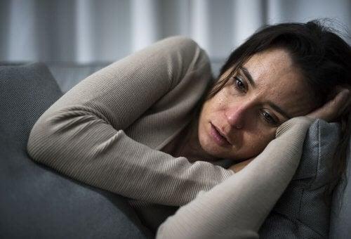 Kvinne med kognitivt oppmerksomhetssyndrom som gråter på sofaen.