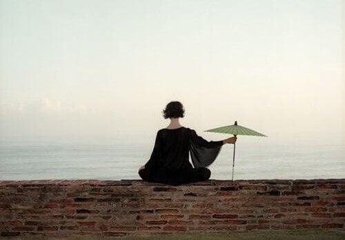 Kvinne med paraply ønsker indre stillhet.