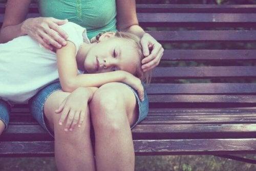 Trist jente med hodet på mors mors ben.