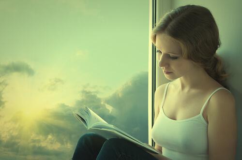jente-leser-bok-ved-et-vindu