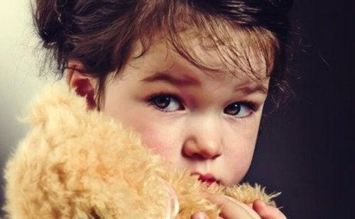 Jente som holder teddybjørn.