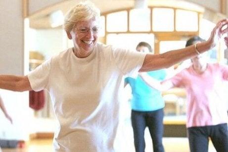 En eldre kvinne danser med et smil i ansiktet