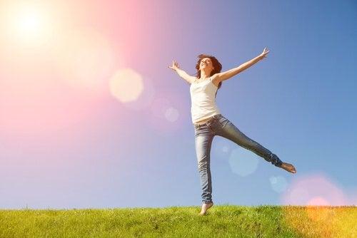 Kvinne som føler lykke og nytelse i solen.