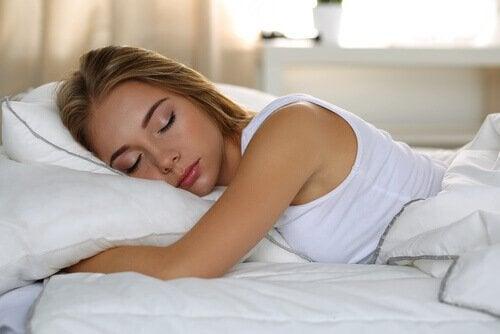 Kvinne som sover i sengen.