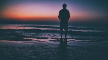 En mann som står ved sjøen, vurderer de negative effektene av å bruke for mye tid alene