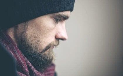 En skjeggete mann ser ned tankefull