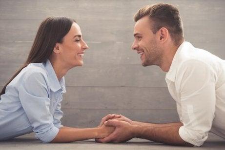 En mann og kvinne holder hender og snakker til hverandre, smiler