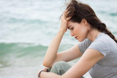 En bekymret kvinne ved sjøen.