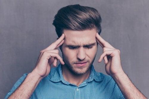 En fyr med øynene lukket prøver å håndtere avsky