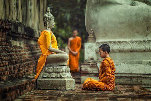 En gutt som sitter foran en statue av Buddha og praktiserer en type av buddhisme