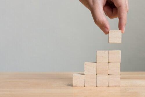 En hånd som plasserer tre kuber på hverandre som lager et tårn.