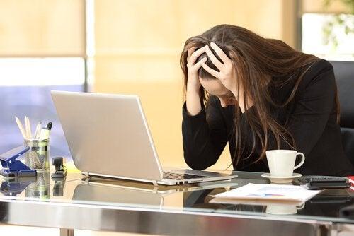 En kvinne er stresset av jobben.