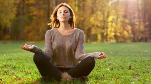 En kvinne mediterer i skogen.